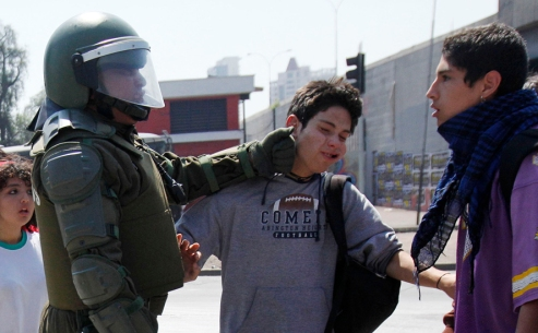 A riot police officer punches a student during a protest against the government and the public state education system at Santiago city