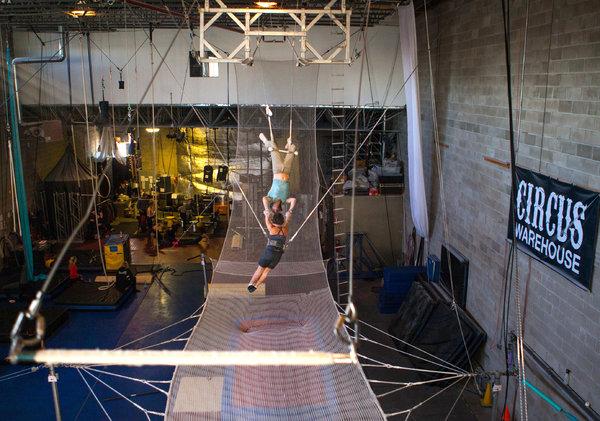 Stuart Moulton, un instructor de trapecio con un estudiante, Leah Ragazzo, en una clase en el Circo del almacén en Long Island City, Queens. Crédito Emon Hassan para The New York Times